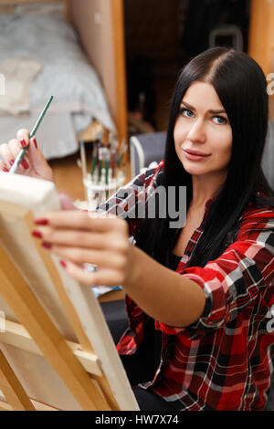 Beautiful long-haired painter at easel - Stock Photo