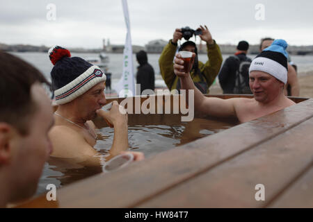 St. Petersburg, Russia, 18th March, 2017. Man drinking hot tea in the tank with warm water after a swim in river - Stock Photo