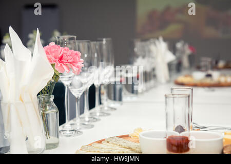 Close up picture of wine glasses with flower in restaurant. Serving ...