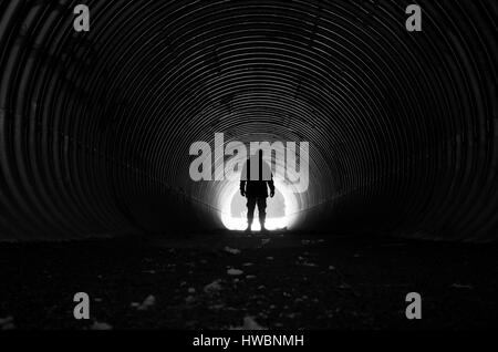 Human standing in dark tunnel with light at other end. Beautiful, mystical and poetic black and white photo. Calm - Stock Photo