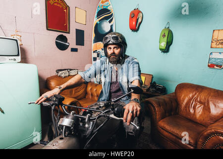 Portrait of mature man indoors, sitting on motorcycle - Stock Photo