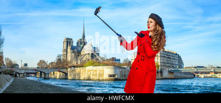 Bright in Paris. happy young traveller woman in red trench coat on embankment near Notre Dame de Paris in Paris, - Stock Photo