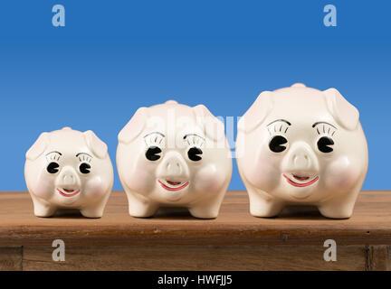 Small medium and large piggy banks on shelf - Stockfoto