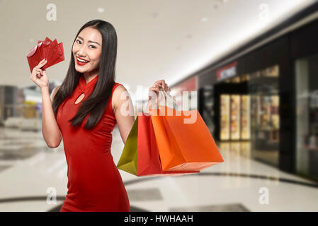 Chinese woman wearing traditional clothes holding shopping bag with mall background - Stock Photo