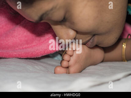 Mother Kissing and Comforting Baby - Stock Photo