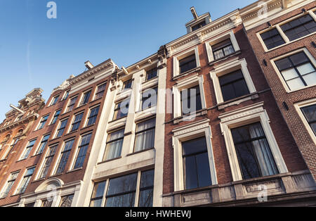 Traditional living houses of old Amsterdam, Netherlands. Facades over blue sky - Stock Photo