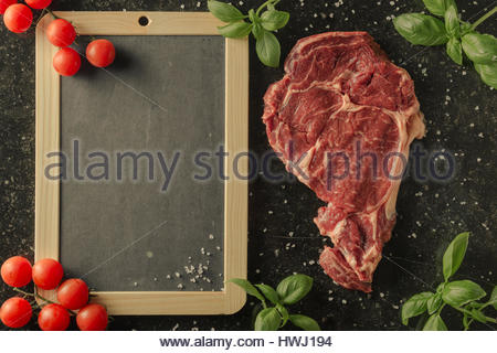 Fresh steak served with spices, tomatoes and leaves of basil on marble background. Uncooked beefsteak with ingredients - Stock Photo