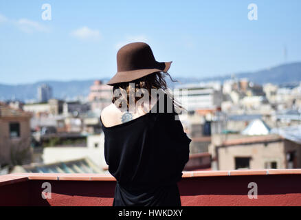 Lonely young woman in brown hat from the back thinking on terraсe, Barcelona, gothic quarter - Stock Photo