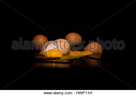 broken egg in black background - Stock Photo