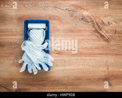 Paint tray and roller, gloves and face mask on wood background - Stock Photo