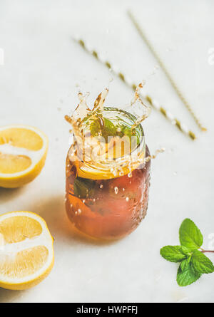 Summer cold Iced tea with lemon and herbs, vertical composition - Stock Photo