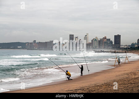 DURBAN, SOUTH AFRICA - MARCH 23, 2017: Three unknown early morning fishermen on beach against overcast Durban city - Stockfoto