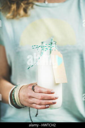 Young woman holding bottle of dairy-free almond milk - Stock Photo
