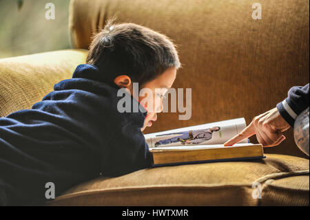 A young boy on a couch reading a big picture book.  A mother's finger pointing.  Close up, natural light, horizontal, - Stock Photo
