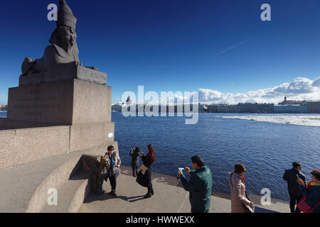 St. Petersburg, Russia, 23rd March, 2017. Chinese tourists make photos against the sphinx on the embankment of river - Stock Photo
