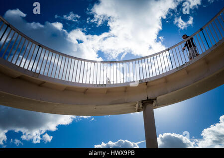 Person walking a dog on spiral bridge - Stock Photo