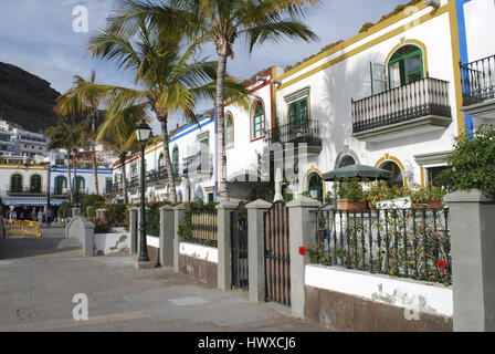White houses, palms, flowers blossom in the evening time. Street view, Puerto de Mogan, Gran Canaria, Spain. - Stock Photo