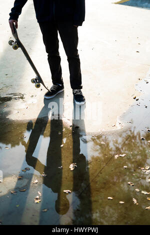 Skateboarder in a skatepark reflected in a puddle - Stock Photo