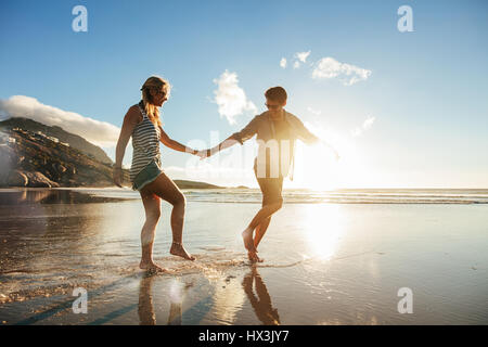 Full length shot of young couple holding hands walking on the beach and having fun. Young man and woman enjoying - Stock Photo