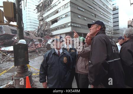 President George W Bush points toward something as he stands among a group of people assessing the damages of the - Stock Photo