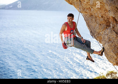 Male rock climber resting while hanging on rope before next attempt on challenging route - Stock Photo