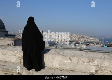 Muslim veiled woman watching the cityscape of Istanbul, Turkey - Stock Photo