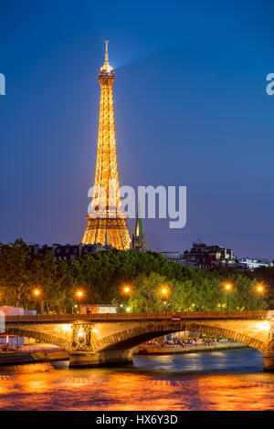 Illuminated Eiffel Tower and Seine River banks in Summer. Paris, France - Stock Photo