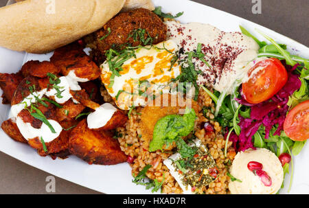 Vegetarian meal consisting of middle east food or mezze, with pitta, baked haloumi, salad, falafel and rice - Stock Photo