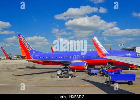 View of parked commercial airplanes at gates being serviced and having luggage loadied in preparation for flight - Stock Photo