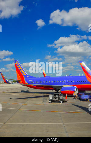 View of parked commerical airplanes at gates being serviced and having luggage loadied in preparation for flight - Stock Photo