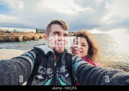We love traveling. Adventure Selfie. Caucasian young couple taking selfie while they walking on mountains near the - Stock Photo