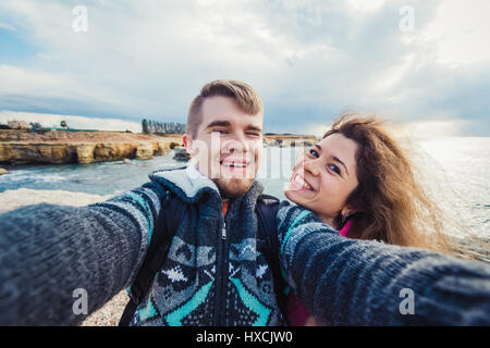 Young happy couple is taking selfie photo on vacation near sea. - Stock Photo