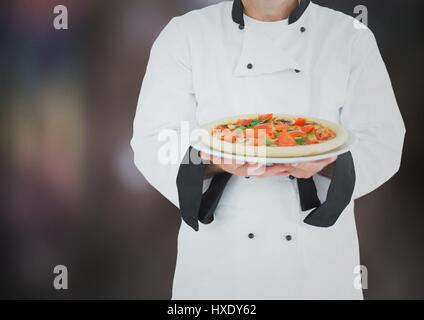 Digital composite of Chef with pizza against blurry dark grey background - Stock Photo