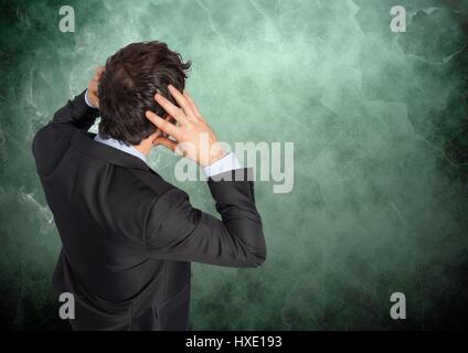 Digital composite of Stressed man against green background with smoke - Stock Photo