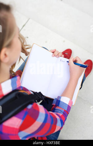 Portrait from above of a girl writing in her diary - Stock Photo