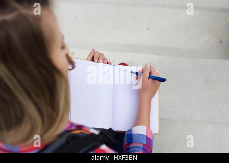 Portrait from top of a young woman writing a to do list in book - Stock Photo