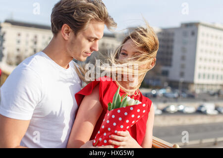 Young couple dating on bridge at windy spring day - Stockfoto
