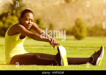 Portrait of young black woman runner stretching legs in the park - Stock Photo