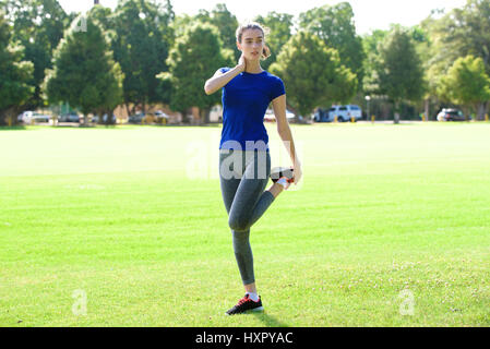 Full length portrait of sporty woman stretching in field - Stock Photo