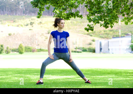 Full length portrait of serious woman stretching outside in summer - Stock Photo