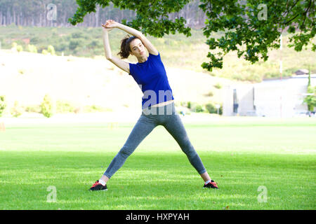Full length portrait of woman stretching outdoors in park - Stock Photo