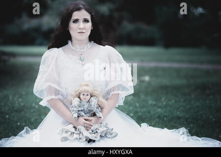 Woman in white Victorian dress in the park - Stock Photo