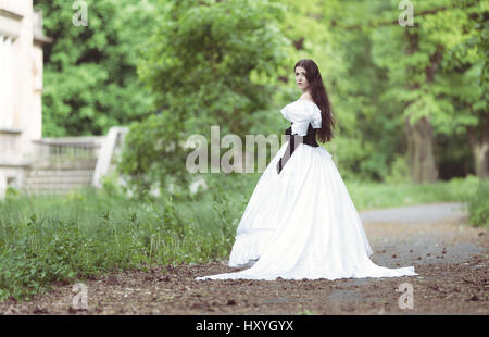 Woman in white Victorian dress in spring park - Stock Photo