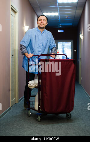 young man pushing a housekeeping cart laden with clean towels stock photo 135204344 alamy. Black Bedroom Furniture Sets. Home Design Ideas