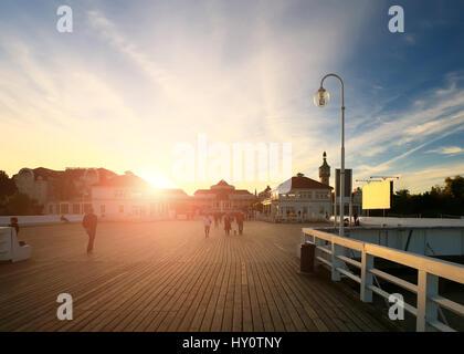 Wide boardwalk at sunset. Bright sun illuminate wooden boardwalk in the evening. Couples walking on boardwalk in - Stock Photo