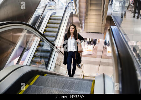 Sweden, Woman on escalator in shopping center - Stock Photo