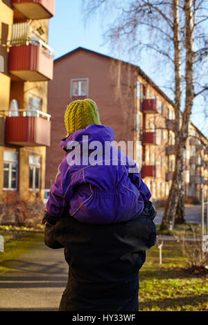 Sweden, Sodermanland, Stockholm, Johanneshov, Hammarbyhojden, Rear view of mid adult woman carrying son (2-3) - Stock Photo