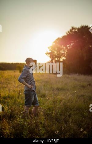 Sweden, Skane, Norra Rorum, Man standing in grassy field at sunset - Stock Photo