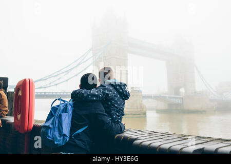 UK, England, London, Mid adult man holding boy (8-9) while looking at Tower Bridge in fog - Stock Photo