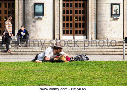 Young couple lying on lawn embracing, young man woman grass - Stock Photo